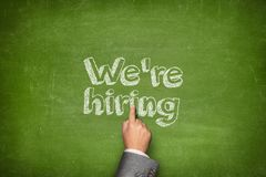 We are hiring concept. On green blackboard with businessman hand stock photos
