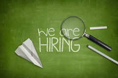 We are hiring concept on green blackboard with. We are hiring concept on green full frame blackboard with magnifying glass stock image