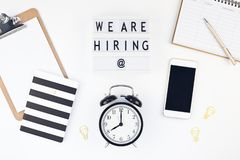 We are hiring flat lay on white background. Creative top view flat lay of desk with we are hiring text on lightbox with copy space on white background in minimal royalty free stock photo