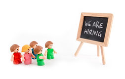 We Are Hiring. A group of toy people looking at We Are Hiring text on a blackboard. White background Royalty Free Stock Images