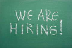 We are hiring!. We are hiring, handwritten with white chalk royalty free stock photo