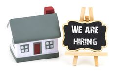 We are Hiring! inscription on a blackboard and miniature model. Of house on a white background royalty free stock photo
