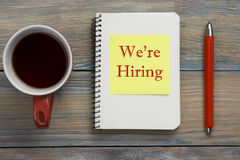 We are Hiring. Office desk table with notepad, pencil and coffe cup. Top view. We are Hiring. Office desk table with notepad, pencil and coffe cup. Top view stock photography