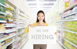 We are hiring sign board in department store. Young Asian woman hand holding `we are hiring` sign board in market or department store Stock Image