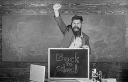 Hiring teachers for new school year. Back to school teachers recruitment. Man bearded holds blackboard inscription back