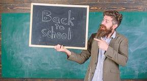 Hiring teachers for new school year. Man bearded holds blackboard inscription back to school. Back to school teachers