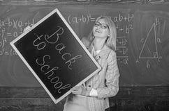 Hiring teachers for new school year. Woman teacher holds blackboard inscription back to school. Looking committed