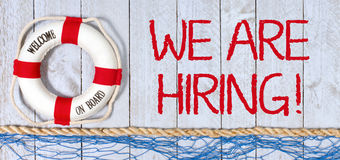 We are hiring - Welcome on Board. Lifebuoy with text on wooden background, recruitment and employment stock image