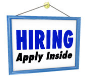 Hiring Window SIgn Apply Within Employment Interview Job. A sign hanging in a store or office with the words Hiring - Apply Inside to advertise an open position Royalty Free Stock Photo