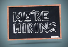 We are hiring written on blackboard. Against grey background Stock Photo