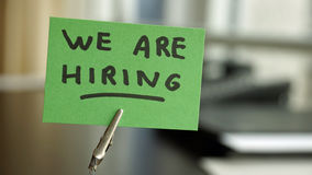 We are hiring written. On a memo at the office stock photography