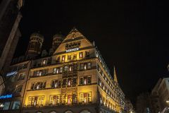 Hirmer在一个传统巴法力亚大厦的百货商店在街市慕尼黑, Frauenkirche教会在背景中能被看见 免版税库存照片