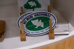 HIROSHIMA, JAPAN - FEB 05, 2018: Stickers of No More Hiroshimas with peace dove for sale in Memorial museum stock photography