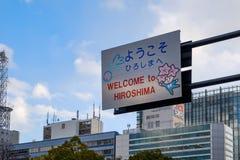 HIROSHIMA JAPAN - FEBRUARI 05, 2018: Välkomnande till det Hiroshima liten medicinflaskatecknet med kawaiiteckenet och blå himmel arkivfoto