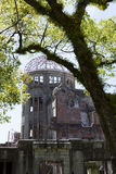 Hiroshima Peace Memorial. Or Atomic Bomb Dome that was bombed in World War II. The metal frame of the dome and destroyed bricks are visible behind the leafy Royalty Free Stock Photos