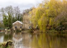 Reflected in the river. Hirst Mill and the colourful trees next to it reflected in the River Aire stock images