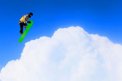 His active sport lifestyle . Mixed media. Snowboard rider jumping against blue cloudy sky Stock Image