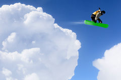 His active sport lifestyle . Mixed media. Snowboard rider jumping against blue cloudy sky Royalty Free Stock Image