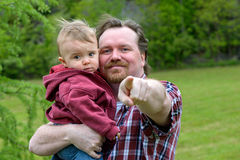 In his Arms. Father holding toddler son both looking at the camera. Father is pointing in the direction of the camera royalty free stock images