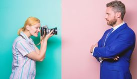 His confidence is her focus. Photographer shooting male model in studio. Businessman posing in front of female stock photography