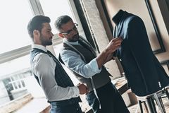 His designs are in demand. Two young fashionable men looking at jacket while standing in workshop royalty free stock photography