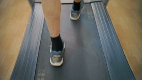 His feet makes heart work. Slow motion close-up shot of male feet walking on treadmill. Every time he coming to the gym he having some cardio stock footage