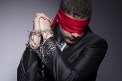 His hands are in chains and his eyes are blindfolded. A man with chains and blindfold standing and looking down. Studio shot Royalty Free Stock Photography