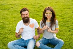 His heart belongs to her. Bearded man giving her a loving heart. Couple in love having photobooth party on green grass stock photos