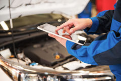 His helper at work. Close-up of man in uniform working on digital tablet while standing in front of car hood in workshop stock photos