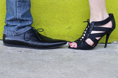 His & Her Shoes Against a Chartreuse Wall Stock Images