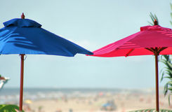 His and Hers Beach Umbrellas. A depth of field shot of a bright sunny beach with a blue umbrella and a pink umbrella standing in front of it Royalty Free Stock Image
