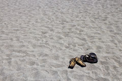 His and hers flip flop sandals on the sandy beach Royalty Free Stock Images