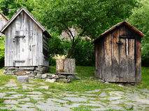 His and Hers Outhouses. Old wooden his and hers outhouses in rustic country setting royalty free stock image