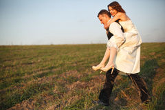 On his own shoulders - groom carries bride across the field Royalty Free Stock Image