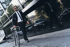 In his own style. Full length of handsome young man in full suit pulling his bicycle while walking outdoors Royalty Free Stock Images