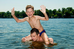 With his son in the water father. Father and son swimming in the river Stock Photography