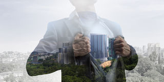 His super abilities for leading business. Confident young businessman posing with cityscape on background Stock Image