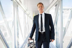On his way to airplane. Confident mature businessman carrying suitcase while walking through a passenger boarding bridge Stock Image