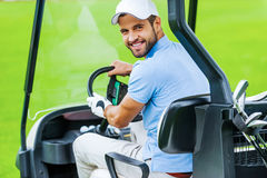 On his way to the next hole. Rear view of young happy male golfer driving a golf cart and looking over shoulder Royalty Free Stock Images
