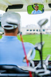 On his way to the next hole. Young happy male golfer driving a golf cart and looking at rear view mirror Royalty Free Stock Image