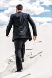 He is on his way to success. Rear view of young man in formalwear rising up by desert dune Stock Images