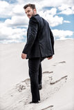 He is on his way to success. Rear view of young man in formalwear rising up by desert dune Royalty Free Stock Photography