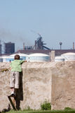 His world. Small boy looking over stone wall at factory pollution Stock Photography