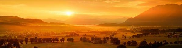 Hisnande morgonlansdcape av den lilla bavarianbyn som täckas i dimma Scenisk sikt av bayerska fjällängar på soluppgång med majest Royaltyfria Bilder