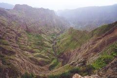 Hisnande panorama av en brant klyfta med ogenomskinlighetsflodbädd och frodig grön vegetation i dalen av det Delgadinho berget arkivfoton