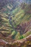 Hisnande panorama av en brant klyfta med slingrig flodbädd och frodig grön vegetation på Delgadinho bergkant arkivbilder