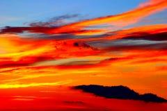 Hisnande röd solnedgång på den blåa himlen med kusliga moln arkivbild