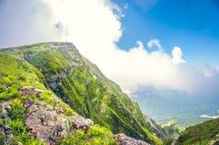 Hisnande sikt för landskap av en dal från ett högt berg på molnnivån på en solig dag arkivbilder