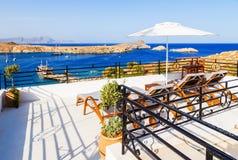 Hisnande sikt på fjärden med stranden och skepp från balkong i Lindos, Rhodes, Grekland Royaltyfria Bilder