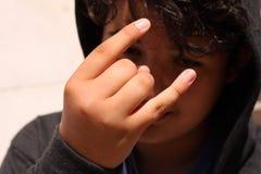 Hispânico incomodado 13 de velha escola anos de adolescente do menino que veste um hoodie que levanta com emoção do diabo da roch foto de stock royalty free